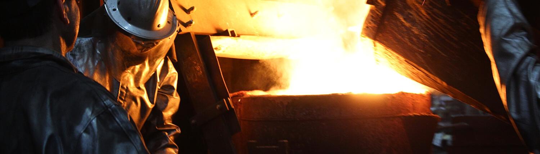 Gießerei Gustav Buchholz - Mitarbeiter gießen flüssiges Metall in einen Behälter. Eisenguss, Grauguss, Sphäroguss, Metallguss.