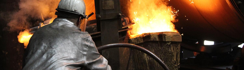 Gießerei Gustav Buchholz - Mitarbeiter gießt flüssiges Metall in einen Behälter. Eisenguss, Grauguss, Sphäroguss, Metallguss.