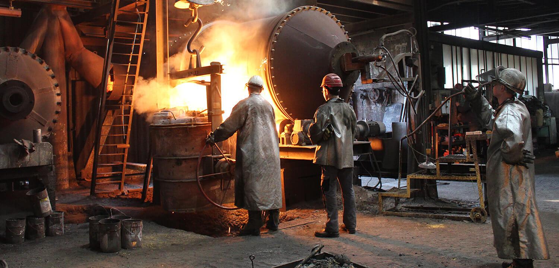 Gießerei Gustav Buchholz - Mitarbeiter stehen vor dem Trommelofen und gießen flüssiges Metall aus diesem in einen Behälter. Eisenguss, Grauguss, Sphäroguss, Metallguss.