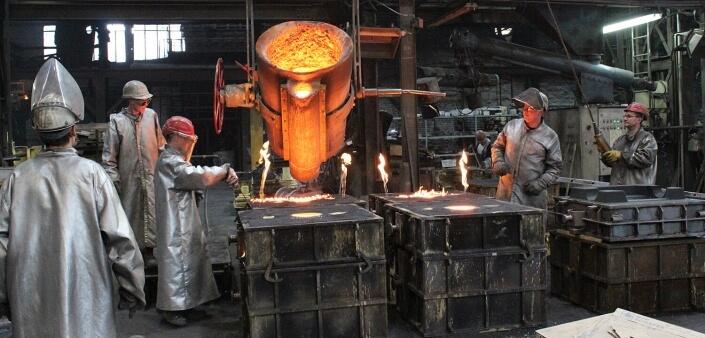 Gießerei Gustav Buchholz - Mitarbeiter beim Guss Prozess. Behälter mit flüssigen Metall wird positioniert.