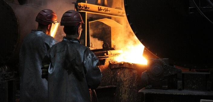Gießerei Gustav Buchholz - Mitarbeiter stehen am Trommelofen und gießen das flüssige Eisen in einen Guss Behälter.